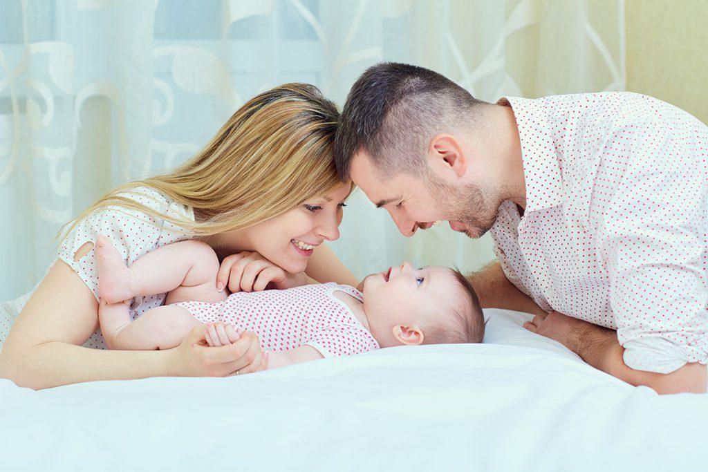 moeder en vader kijken naar de pasgeboren baby