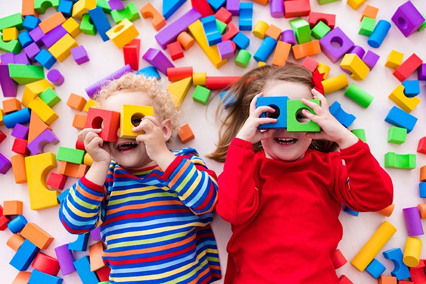 twee kinderen spelen liggend op de grond met gekleurde blokken