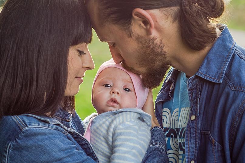 vader en moeder kussen de pasgeboren baby