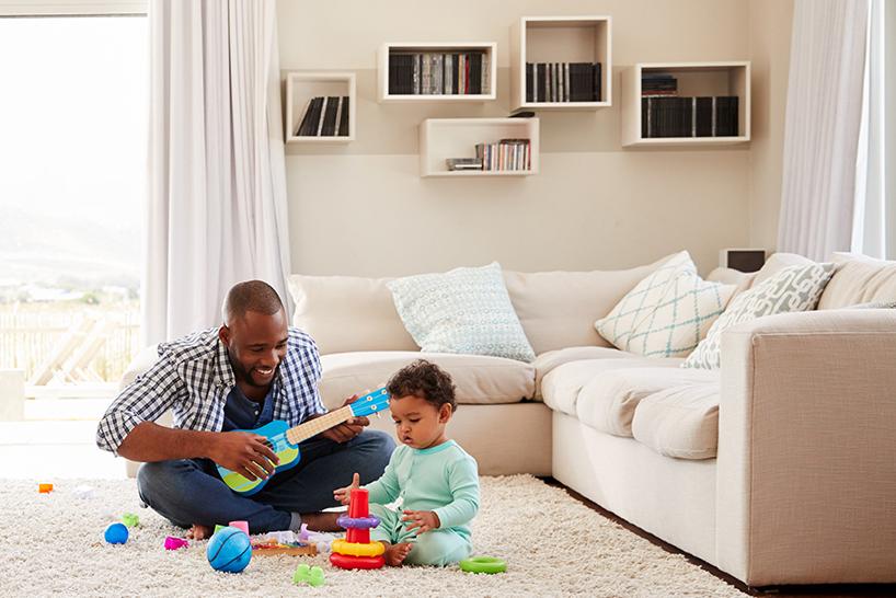 vader en peuter spelen samen met speegoed in een woonkamer