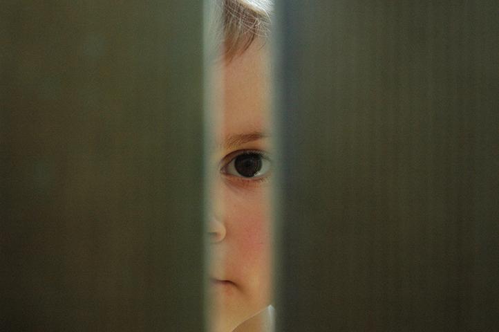 kind kijkt door een kier